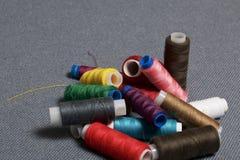 Bobines du fil de différentes couleurs sur un fond tissé gris Images stock