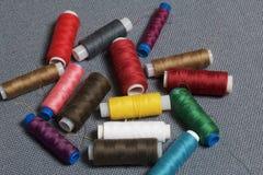 Bobines du fil de différentes couleurs sur un fond tissé gris Photos libres de droits