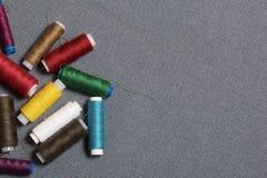 Bobines du fil de différentes couleurs sur un fond tissé gris Images libres de droits