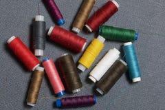 Bobines du fil de différentes couleurs sur un fond tissé gris Photos stock