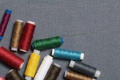 Bobines du fil de différentes couleurs sur un fond tissé gris Image stock