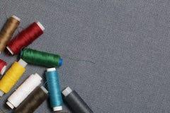 Bobines du fil de différentes couleurs sur un fond tissé gris Photographie stock libre de droits