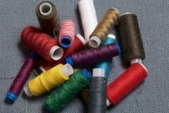 Bobines du fil de différentes couleurs sur un fond tissé gris Photo libre de droits