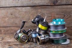 Bobines et spoole de pêche avec la ligne sur le fond en bois Photos libres de droits