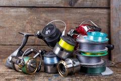Bobines et spoole de pêche avec la ligne sur le fond en bois Photographie stock