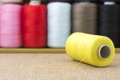 Bobines jaunes de fil sur la toile à sac Photographie stock libre de droits