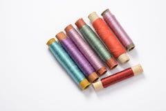 Bobines multicolores avec des fils pour coudre sur le fond blanc Images stock