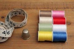 Bobines multicolores, ruban métrique et dé de coton sur un en bois Photos stock