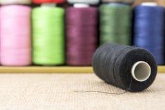 Bobines noires de fil sur la toile à sac Photos stock