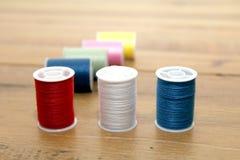 Bobines ou bobines multicolores de coton sur une étiquette en bois de couture Image libre de droits