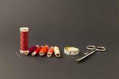 Bobines rouges de fil avec des ciseaux Images libres de droits