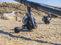 Bobines sur les cannes à pêche sur le plan rapproché de bord de la mer Photos stock
