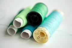 Bobines vertes et bleues de fil sur la table Image libre de droits