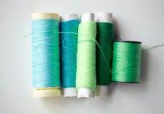 Bobines vertes et bleues de fil sur la table Images libres de droits