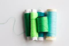 Bobines vertes et bleues de fil sur la table Images stock