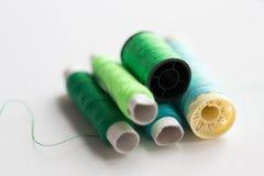 Bobines vertes et bleues de fil sur la table Image stock