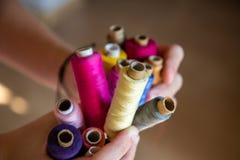 Bobins colorido nas mãos das meninas foto de stock royalty free