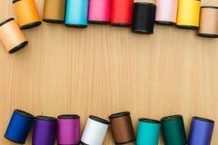 Bobiny z kolorowymi niciami na drewnianym stołowym tle, Szy Zdjęcia Royalty Free