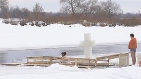 BOBRUISK, ΛΕΥΚΟΡΩΣΙΑ - 19 ΙΑΝΟΥΑΡΊΟΥ 2019: Τα άτομα και τα κορίτσια βαπτίσματος διακοπών λούζουν σε μια πάγος-τρύπα το χειμώνα, σ φιλμ μικρού μήκους