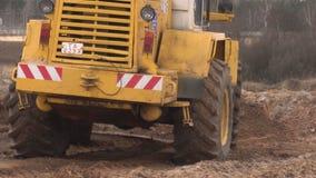 Bobruisk, Λευκορωσία - 20 Μαρτίου 2019: Ο μεγάλος κίτρινος φορτωτής τρακτέρ προγραμματίζει και επίπεδα το έδαφος για την κατασκευ απόθεμα βίντεο