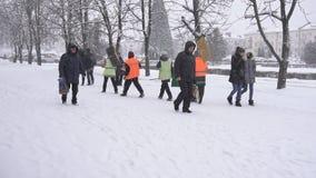 BOBRUISK, BELARUS - 14 JANVIER 2019 : Les portiers dans des gilets de signal avec des pelles passent par la ville d'hiver, mouvem banque de vidéos