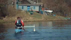 Bobruisk, Belarus - 11 May 2019: Rear view of Athlete rowing on the river in a canoe. Rowing, canoeing, paddling. Training. Kayaking. Man guy is rowing against stock video footage