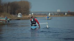 Bobruisk, Belarus - 11 May 2019: Rear view of Athlete rowing on the river in a canoe. Rowing, canoeing, paddling. Bobruisk, Belarus - 11 May 2019: Athlete rowing stock footage