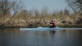 Bobruisk, Belarus - 11 May 2019: Tracking shot of handicapped sportsman rowing on the river in a canoe. Rowing, canoeing. Bobruisk, Belarus - 11 May 2019 stock video footage