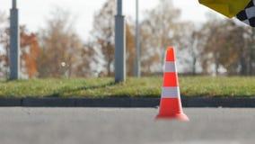 BOBRUISK BIAŁORUŚ, PAŹDZIERNIK, - 21, 2018: Karting rywalizacja arbiter macha koniec flagę przy konem, zwolnione tempo zdjęcie wideo