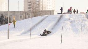 BOBRUISK BIAŁORUŚ, STYCZEŃ, - 12, 2019: Dzieci na pogodnym mroźnym dniu jadą od śnieżnego wzgórza, zima, wolny mo zbiory wideo