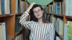 Bobruisk, Bielorrússia - 11 de abril de 2019: Retrato da menina bonita nova na biblioteca Estudante fêmea que estuda entre o lote filme