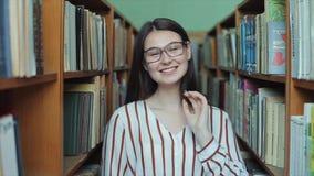 Bobruisk, Bielorrússia - 11 de abril de 2019: Retrato da menina bonita nova na biblioteca Estudante fêmea que estuda entre o lote vídeos de arquivo
