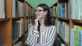 Bobruisk, Bielorrusia - 11 de abril de 2019: Retrato de la muchacha hermosa joven en biblioteca Estudiante que estudia entre la p almacen de metraje de vídeo