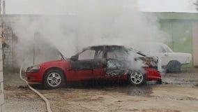 BOBRUISK, BIELORRUSIA - 25 DE JULIO DE 2018: los bomberos o los bomberos con la manguera extinguen un coche ardiente después del  metrajes
