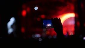 Bobruisk, Bielorrusia - 6 de julio de 2018: los lanzamientos desconocidos de la persona en smartphone durante el concierto del Bi metrajes