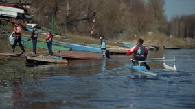 Bobruisk, Bielorrusia - 11 de mayo de 2019: Atleta que rema en el río en una canoa Hombre que se acerca al muelle El remar, canoe almacen de video