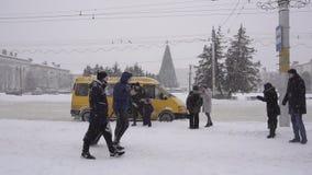 BOBRUISK, BIELORUSSIA - 14 GENNAIO 2019: La gente nella città sta aspettando alla fermata dell'autobus il trasporto, sta nevicand stock footage