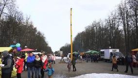 BOBRUISK, BIELORUSSIA 03 09 19: La gente cammina nel parco della città lungo le stalle dell'alimento e un palo di legno di Maslen stock footage