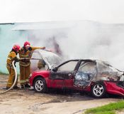 BOBRUISK, BIELORUSSIA - 25 LUGLIO 2018: Due vigili del fuoco estinguono un'automobile bruciante, fuoco Fotografia Stock Libera da Diritti