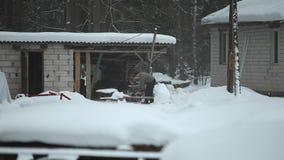 Bobruisk, Weißrussland - 12. Januar 2019: Erwachsener Mann, der Holz auf schneebedecktem Yard für ein Haus hackt Winterlandschaft stock footage