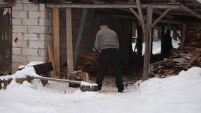 Bobruisk, Weißrussland - 12. Januar 2019: Erwachsener Mann, der Holz auf schneebedecktem Yard für ein Haus hackt Winterlandschaft stock video