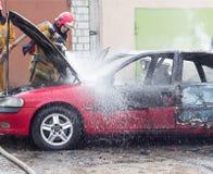 BOBRUISK, WEISSRUSSLAND - 25. JULI 2018: Zwei Feuerwehrmänner löschen ein brennendes Auto, Feuer aus lizenzfreies stockbild