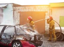 BOBRUISK, WEISSRUSSLAND - 25. JULI 2018: Zwei Feuerwehrmänner löschen ein brennendes Auto, Feuer aus stockbilder