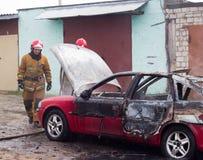 BOBRUISK, WEISSRUSSLAND - 25. JULI 2018: Zwei Feuerwehrmänner löschen ein brennendes Auto, Feuer aus lizenzfreies stockfoto