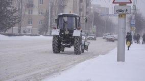 Bobruisk, Wit-Rusland - Januari 14, 2019: Een oude tractor voor de ritten van de sneeuwverwijdering aan een de winterstad, sneeuw stock videobeelden