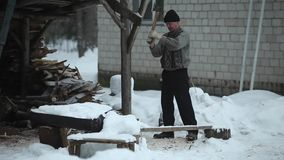 Bobruisk, Wit-Rusland - Januari 12, 2019: Volwassen mensen hakkend hout op sneeuwyard voor een huis De winterplatteland dorp stock video