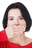 Boca adolescente de la cubierta de la mujer con la mano Fotos de archivo libres de regalías