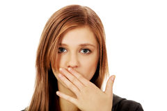 Boca adolescente de la cubierta de la mujer con la mano Fotos de archivo