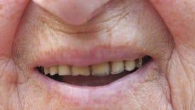 Boca ascendente cercana de la abuela que sonríe y que muestra los dientes amarilleados Mujer mayor con la piel arrugada que ríe e almacen de metraje de vídeo