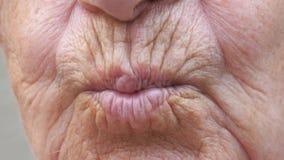Boca ascendente cercana de la vieja abuela que env?a beso del aire en c?mara Mujer mayor con la piel arrugada que hace gesto que  almacen de metraje de vídeo